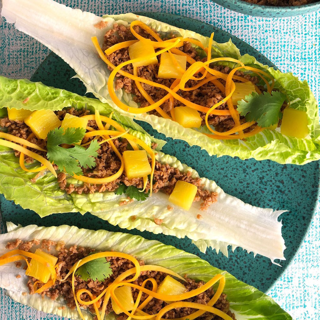 Topdown view of three lettuce wraps, with a TVP mixture in romaine lettuce leaves. Each leaf is topped with pineapple, raw butternut squash, and cilantro.