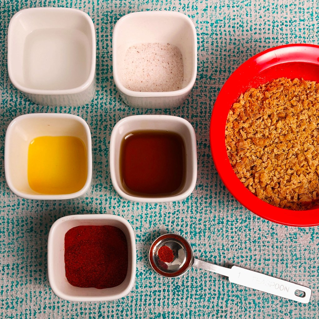 Topdown view of ingredients in vegan bacon bits. Small white dishes contain: water, salt, liquid smoke, maple syrup, and smoked paprika. A red bowl contains TVP, aka textured vegetable protein.