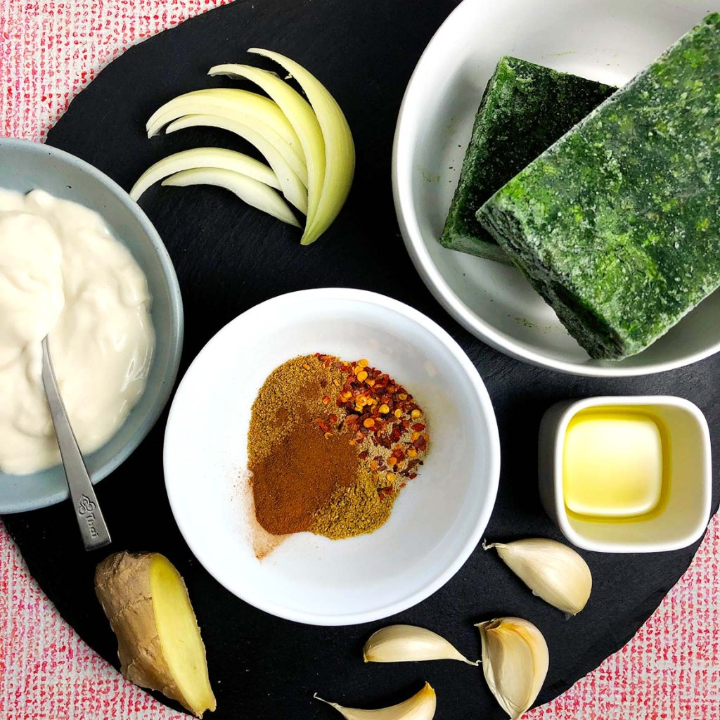 Topdown view of ingredients in Indian-Spiced Spinach (Saag). From top right: slices of white onion, bowl with frozen blocks of spinach, oil, garlic, a white bowl containing spices, a slice of ginger, and yogurt.