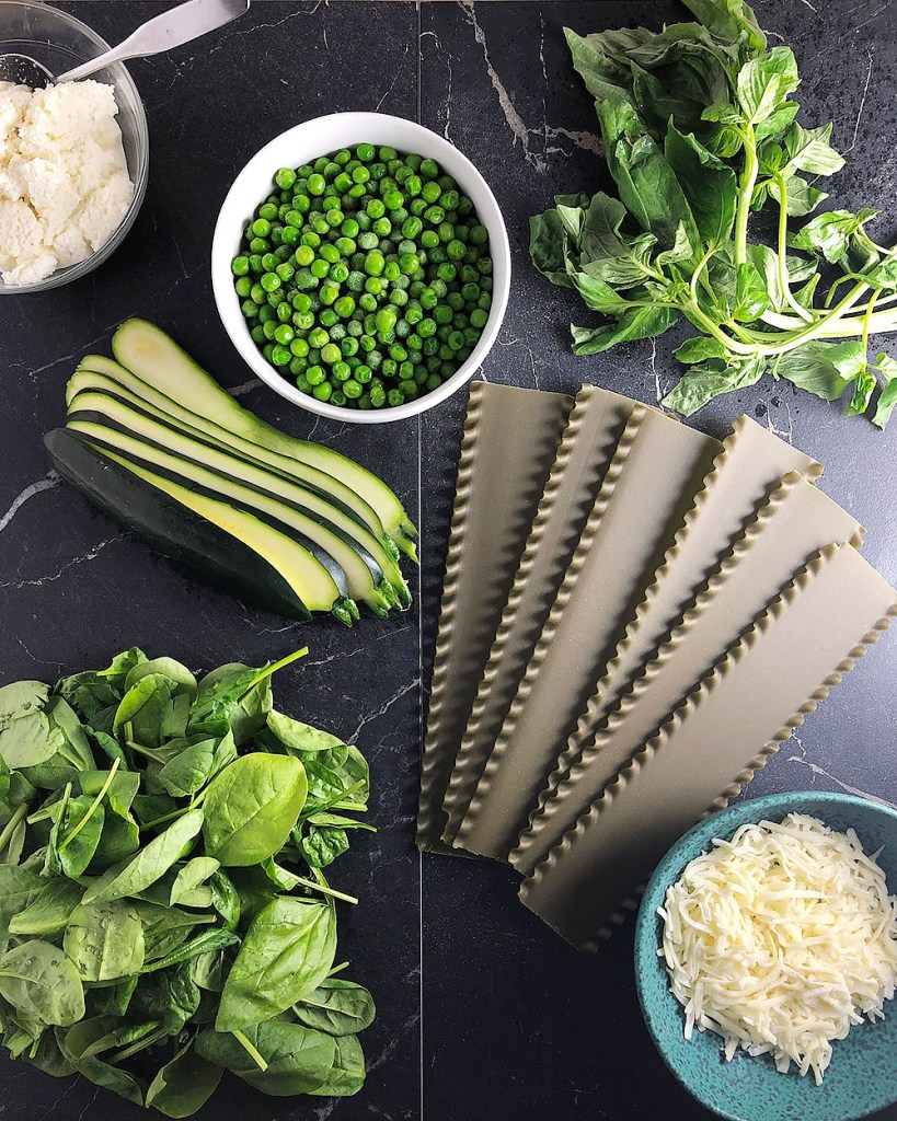 Top down shot of ingredients for green lasagna. All ingredients are on a black marble surface. From the top left - ricotta cheese, frozen peas, fresh basil, spinach lasagna noodles, shredded mozzarella cheese, fresh spinach, zucchini.