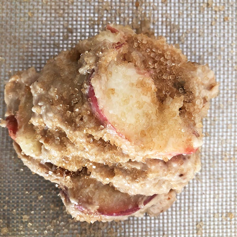 Top-down view of Donut Peach Scone batter on cookie sheet, showing turbinado sugar on top