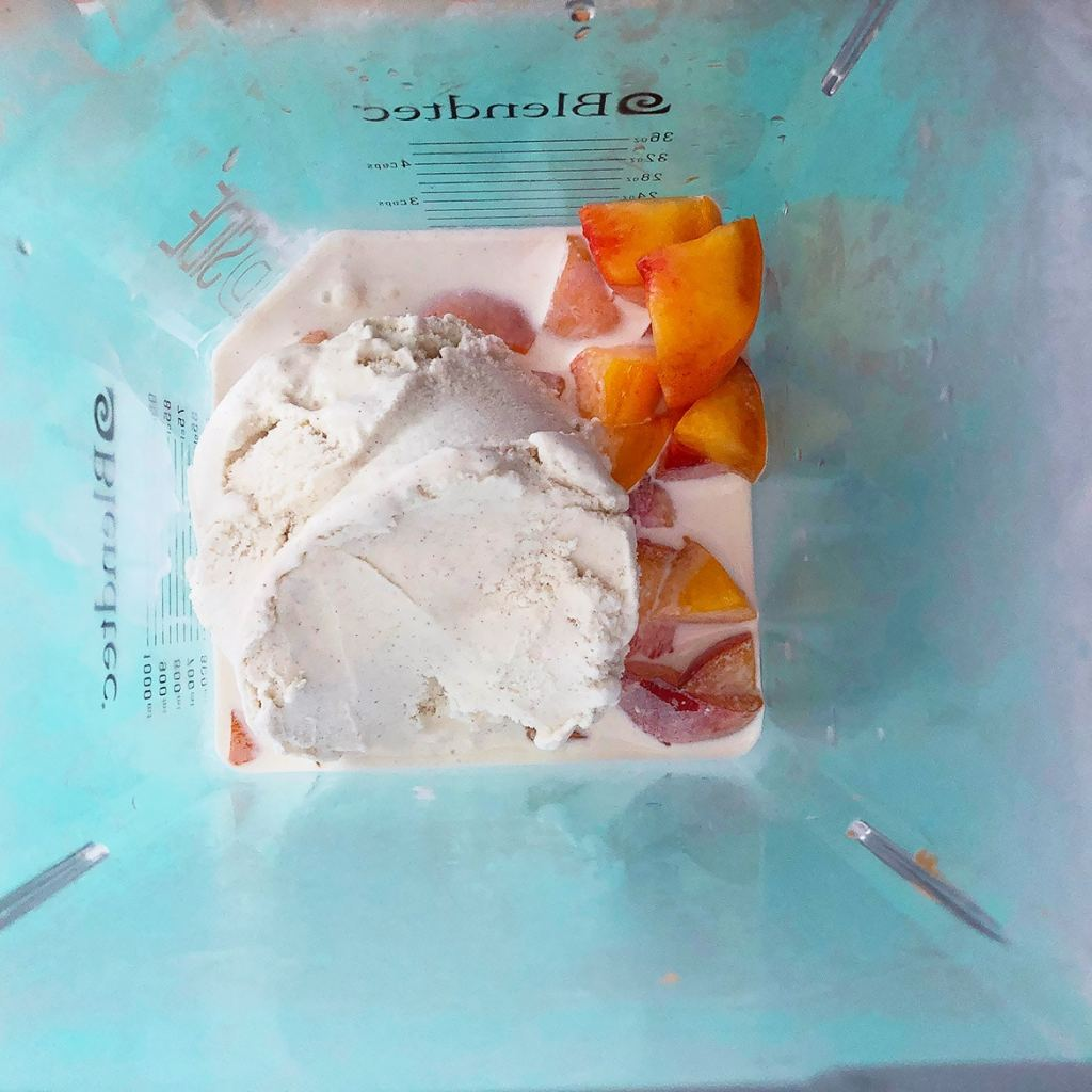 Topdown view of ingredients for peach milkshake in a blender, fresh fruit, cream, and ice cream.