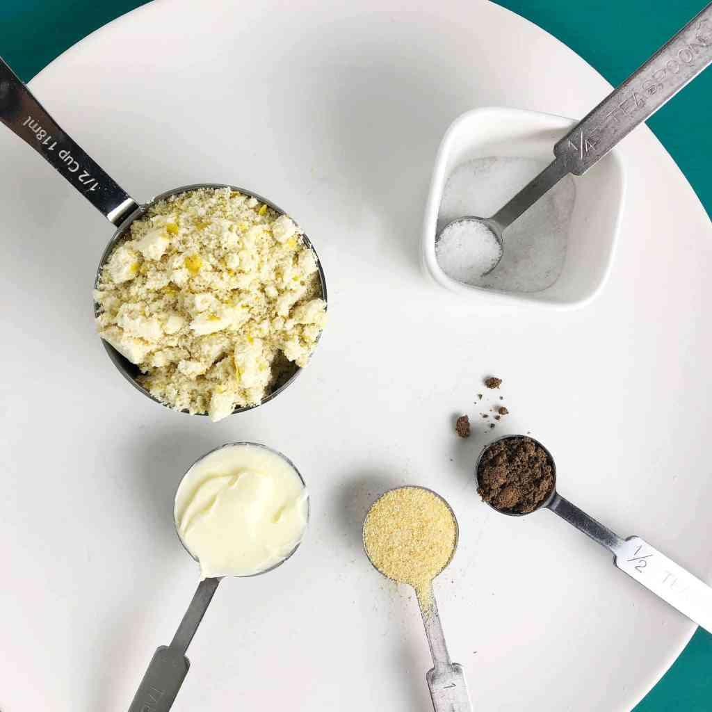 Top-down shot of ingredients for Vegan Scalloped Potatoes. Clockwise from top left: Mother Mix, salt, nutmeg, garlic powder, margarine