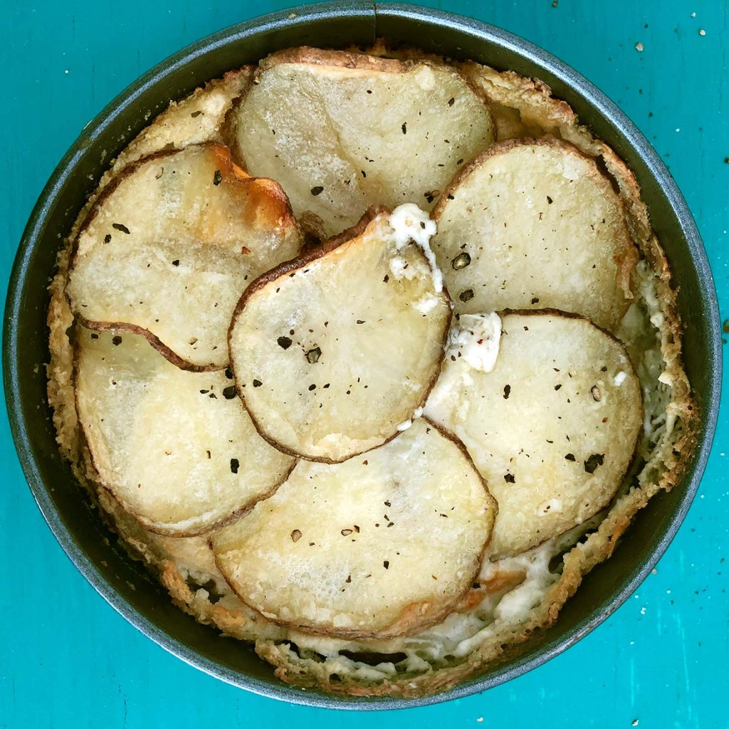 Top-down view of cooked Scalloped Potatoes in baking dish on teal background
