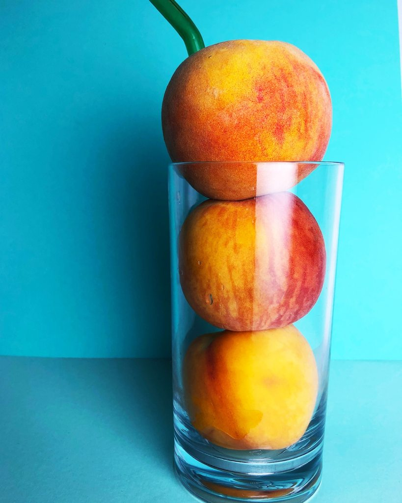 Side view of three peaches in a tall glass with a straw, against a blue background