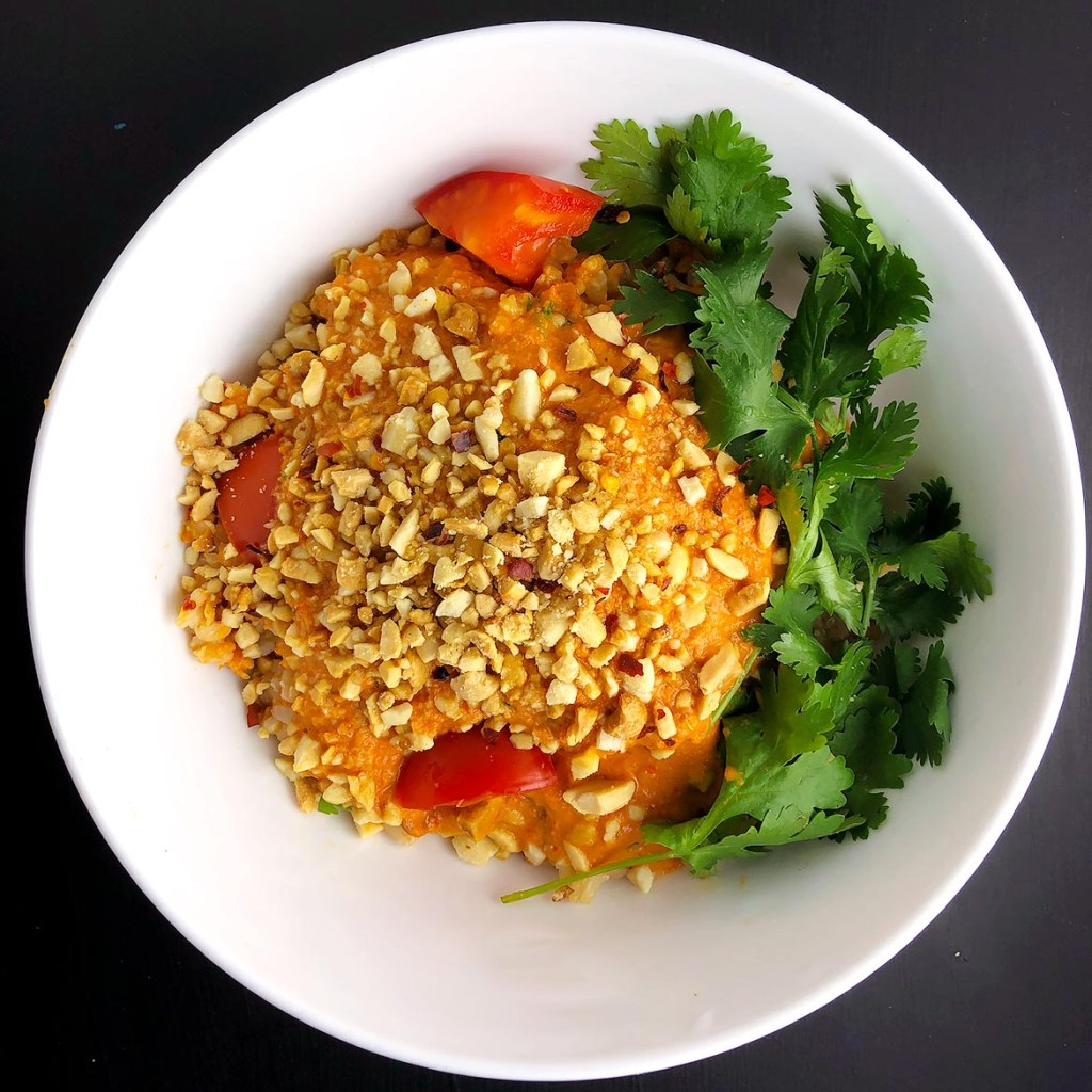 Top-down view of Spicy Tomato Peanut Sauce on brown rice, garnished with chopped peanuts and cilantro