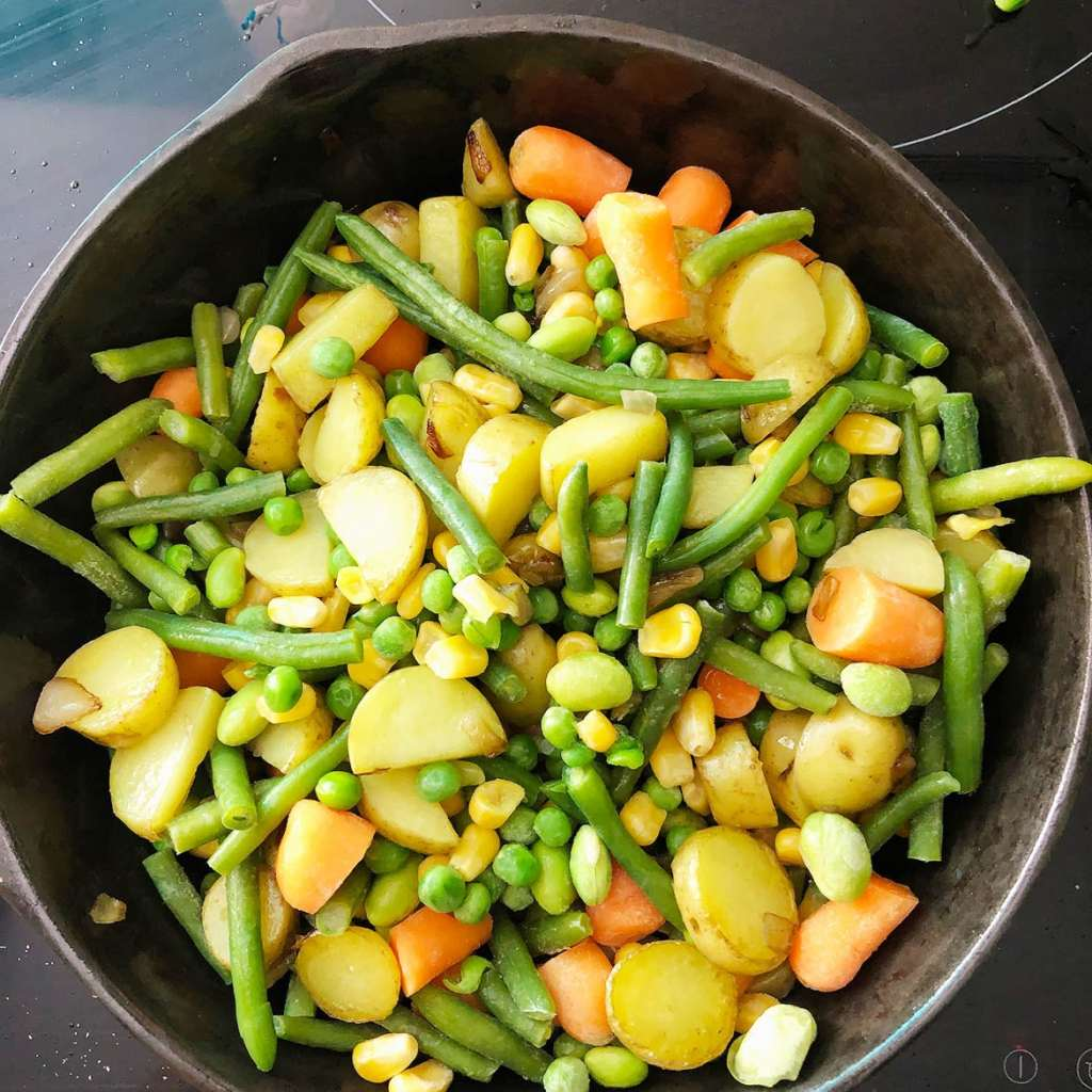 Top-down shot of mixed veggies in frying pan with potatoes and onions. Step 3 for making Veggie Pot Pie.