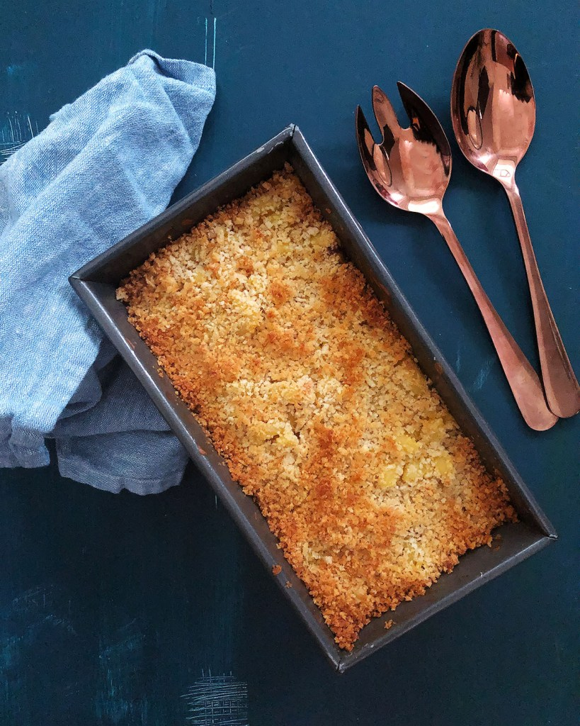 Top-down view of baking pan with Acorn Squash Mac and Cheese, topped with panko topping.