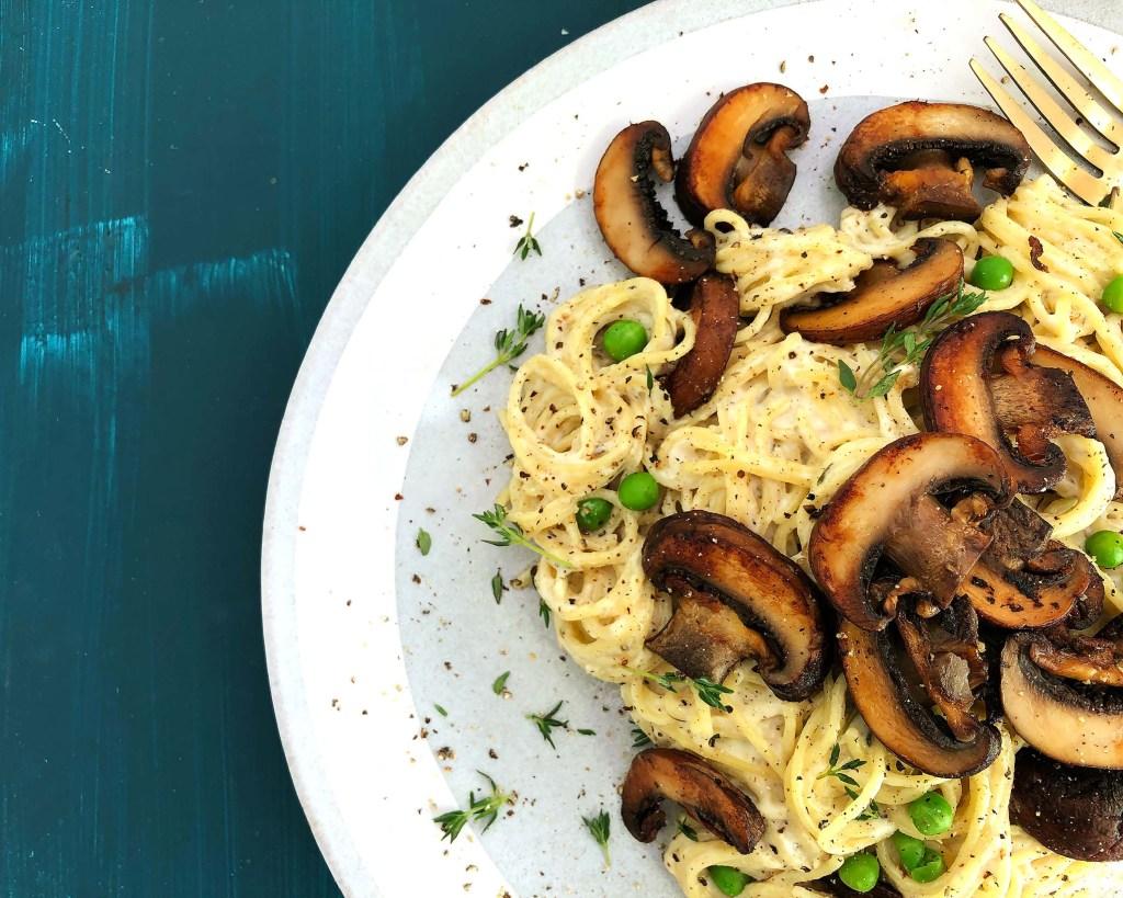 Top-down shot of Mushroom Tetrazzini, with mushrooms and peas in a vegan cream sauce.