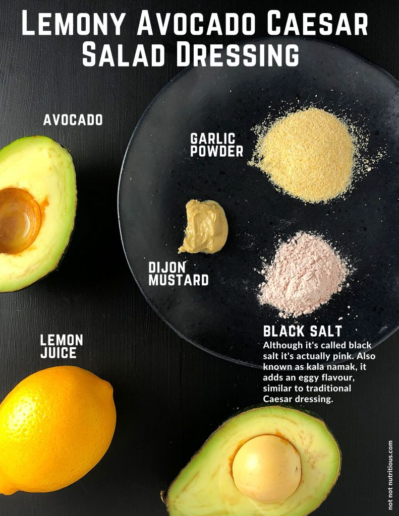 Infographic with a photograph of all the ingredients in Lemony Avocado Casesar Salad Dressing. Top-down shot shows half an avocado and a lemon, along with small amounts of garlic powder, dijon mustard, and black salt on a black plate. Text underneath black salt reads: Although it's called black salt it's actually pink. Also know as kala namak, it adds an eggy flavour, similar to traditional Caesar dressing.