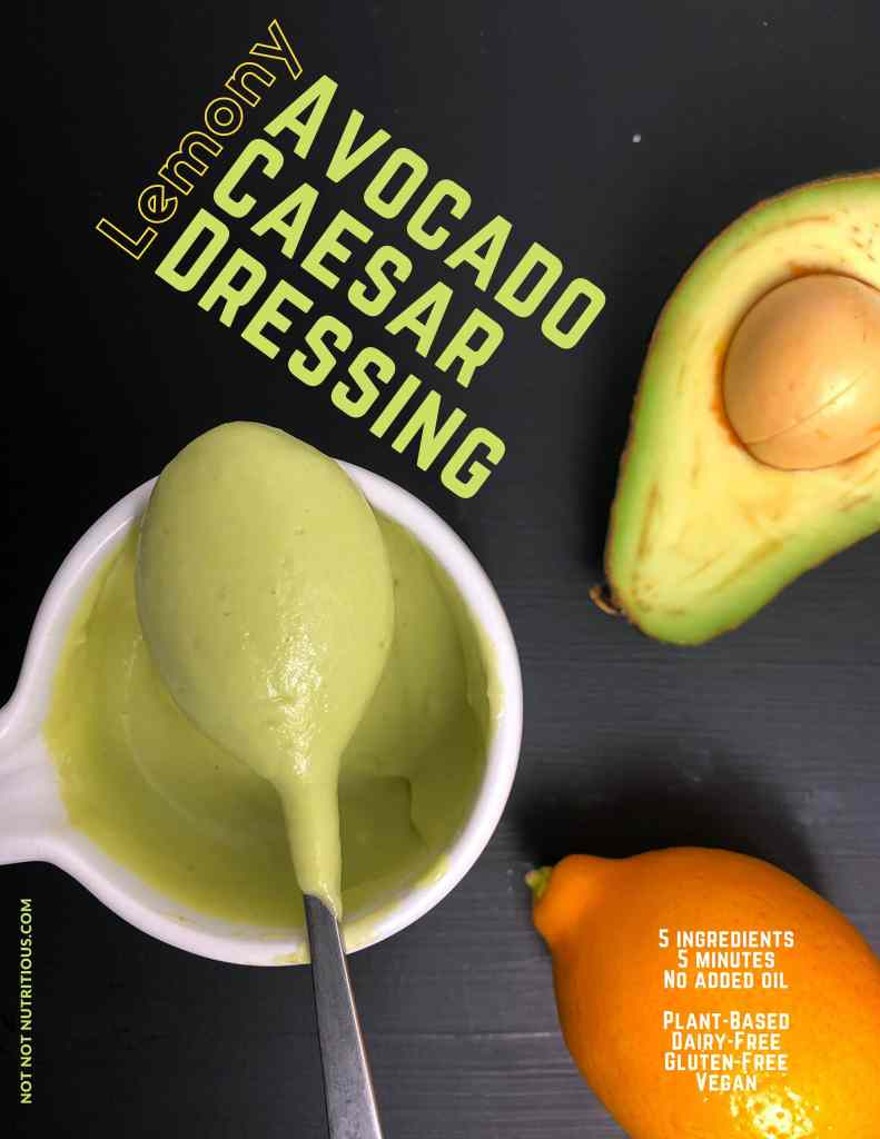 Photo showing spoonful of Avocado Caesar Dressing on a black surface with a halved avocado and a lemon. Text reads: Lemony Avocado Caesar Dressing. 5 ingredients, 5 minutes, no added oil, plant-based, dairy-free, gluten-free, vegan