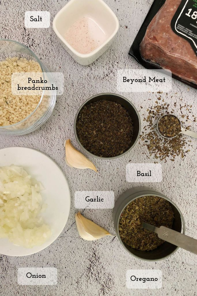 Top-down shot of ingredients in Beyond Meat meatballs. From top right: package of Beyond Meat, dried basil, dried oregano, diced onion, fresh garlic, panko breadcrumbs, and salt. Not pictured, oil for frying onions and garlic.