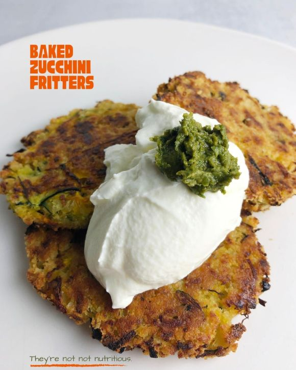 Pinterest graphic for Baked Zucchini Fritters, showing close-up, front view of three Zucchini Fritters, topped with yogurt and pesto.