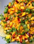 Top-down close up view of Nectarine Salsa, made with nectarines, tomatoes, cilantro, bird's eye chilis, shallots, lime juice, and sweetener.