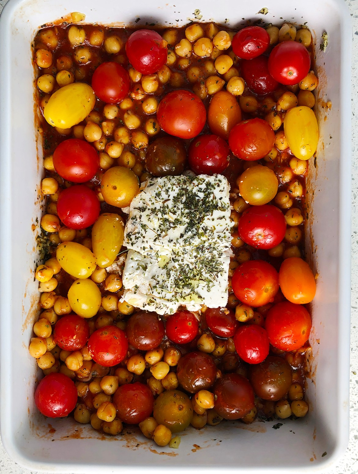 Top down image of white casserole dish with unbaked version of Chickpea Feta Bake, showing yellow and red cherry tomatoes, chickpeas, and feta cheese sprinkled with dried mint and olive oil.