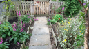 Part of my garde.  Fence and gate made from pallets and 'wombled' divan frames. Paving slabs from Freecycle