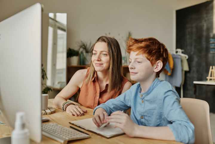 photo of woman and boy smiling while watching through imac