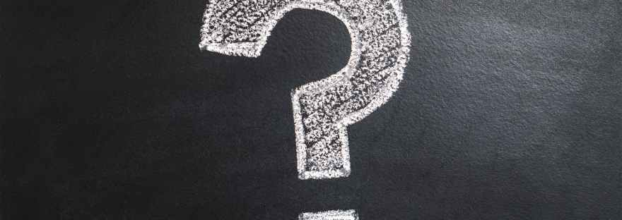 A black board displaying a white question make in chalk that's also coloured in, in white.