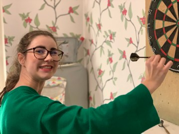 Myself in a green knitted dress, hair in a ponytail, I am holding a dart aiming for the dart board which is with touching distance. The background is creme wallpaper with branches of holly.