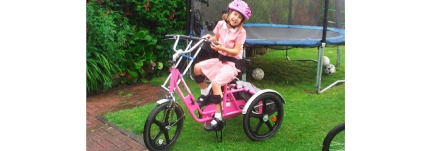 A image of me as a child on my pink trike in the garden (the trampoline is behind ) I am in a red checked school dress and I have a purple helmet on.