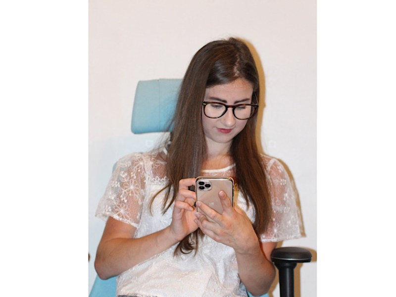 Myself sat on a duck egg computer chair with head rest, against a white background looking at my iPhone. Wear a white blouse with outlines of small flowers. I have my glasses on and my brown hair is straight.