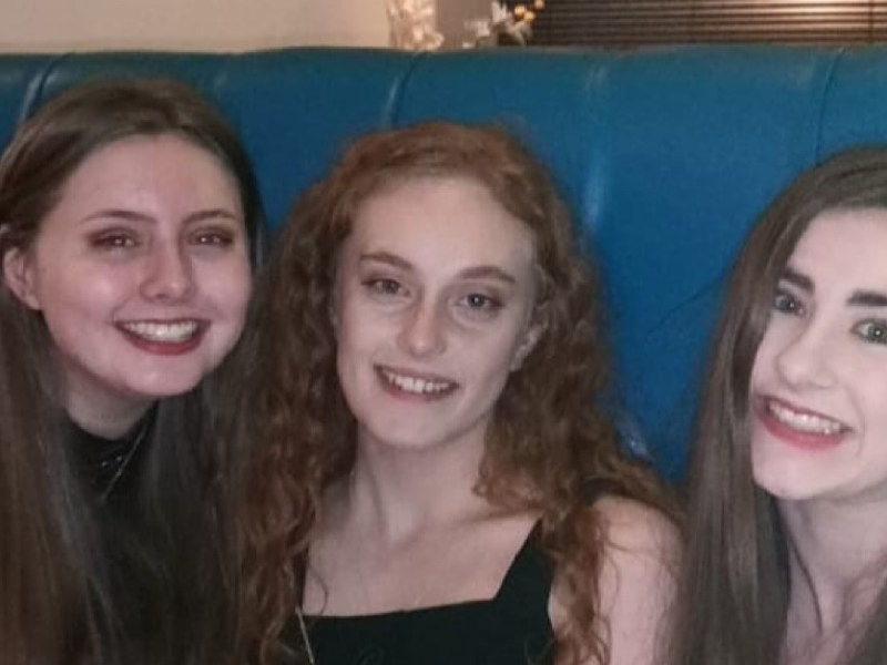 Theres 3 of us sat on a Chesterfield high back blue booth style sofa. I am on the right side with straight hair, my friend with curly hair and a black dress in sat in the middle and then on the end my friend has straight hair and it is a sparkly dress.