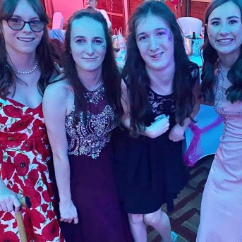 Myself with 3 other friends at the CP Teens UK annual ball. I have a pink dress on on the right, my friends next to me is wearing dark purple with dark hair. Next to her my other friend with dark hair is in burgundy and my friend on the end has a dress with poppies