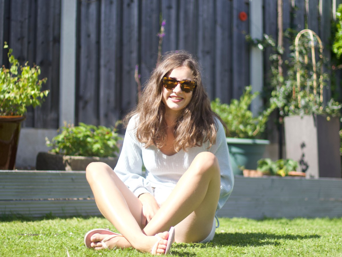 Georgia sat with curly hair and her sun glasses on, on the grass. She has crossed legs and in wearing a light blue top.