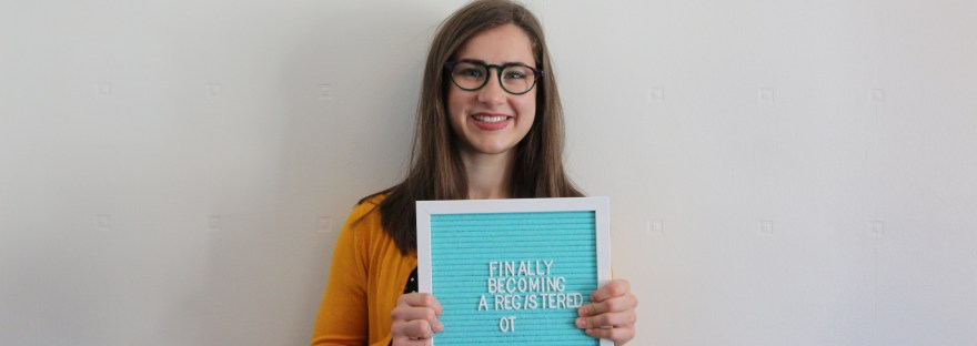 """Georgia a white female with glasses on and brunette shoulder length hair wearing a yellow cardigan. She is holding a blue let board that says """"Finally Becoming A Registered OT""""."""