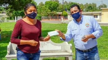 Armando Solís entregando un cheque del programa de empleo temporal.