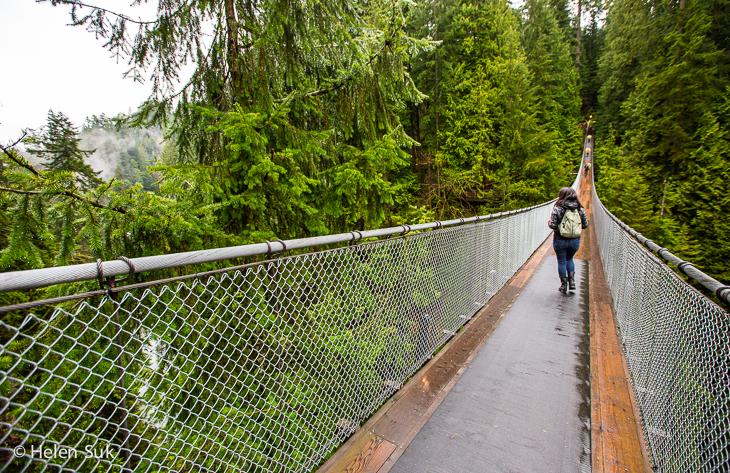 woman walks across the suspension bridge at capilano suspension bridge park vancouver