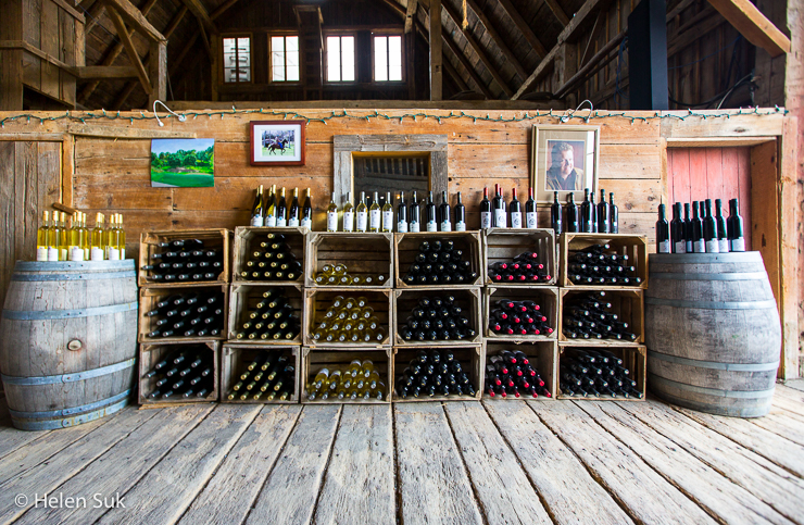 wall lined with bottles of wine inside the old barn at karlo estates