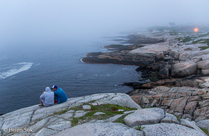 two men sit on the rocks on a foggy evening at peggys cove