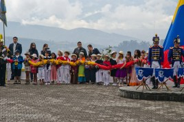 Children representing all of Ecuador hold the flag before it is raised.