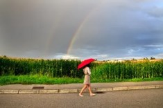 Woman walkign in rain with red umbrella
