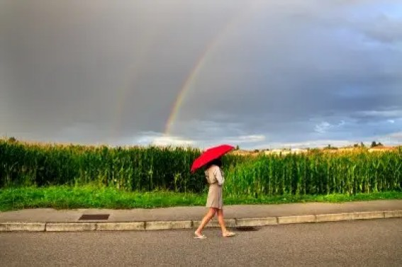 Woman walkign in rain with red umbrella