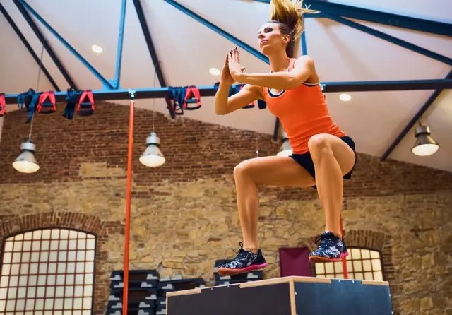 woman in orange top and shorts doing box jumps