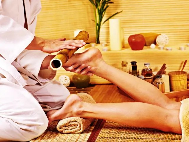 woman having her foot massaged with a bamboo cane as part of a bamboo massage