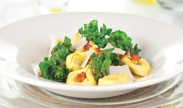 kalettes with tortellini pasta served in a white bowl