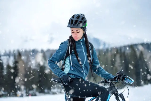 woman on bike with snow falling around her