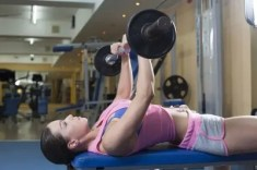 Woman lifting barbell over her chest