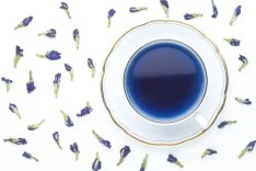 butterflower pea tea leaves around a cup of blue tea