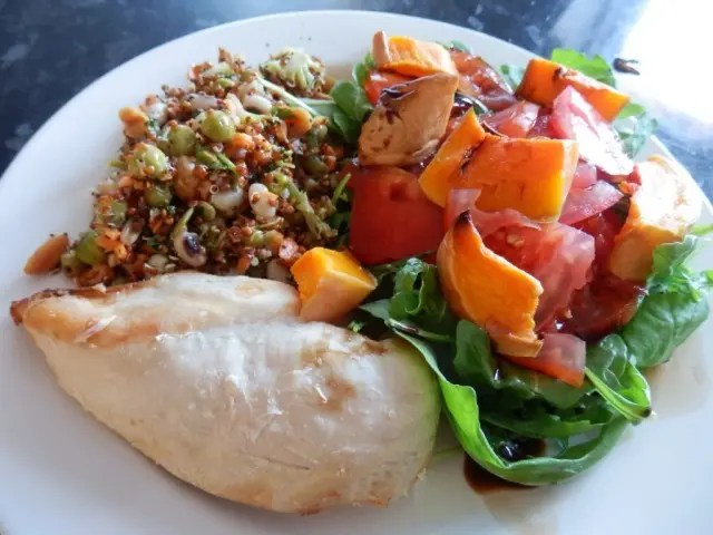 Chicken breast served with bright coloured salad and grains