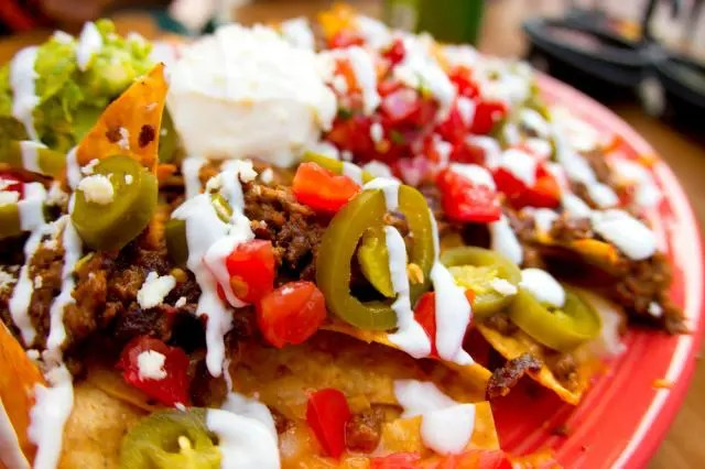 Plate of nachos topped with jalapenos, salsa and beans