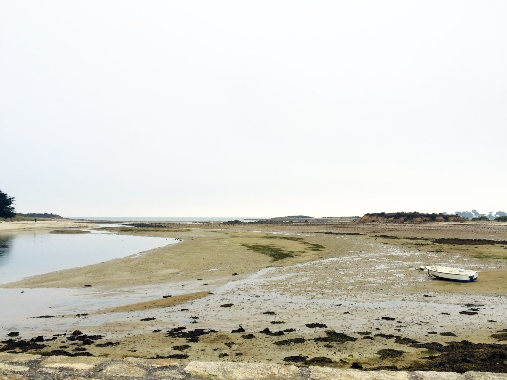 A view of the sea from Carnac, France, with boat beached in the tidal flats.