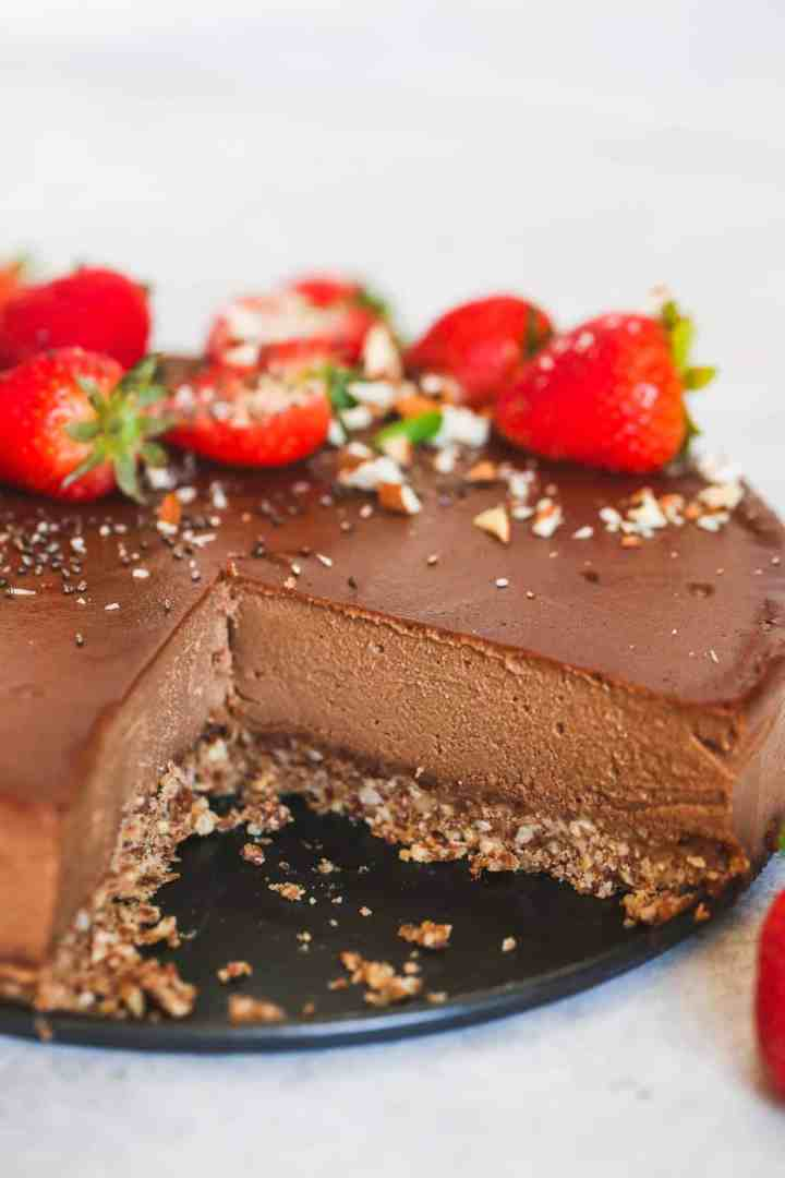 closeup photo of a chocolate cheesecake topped with strawberries with a slice removed