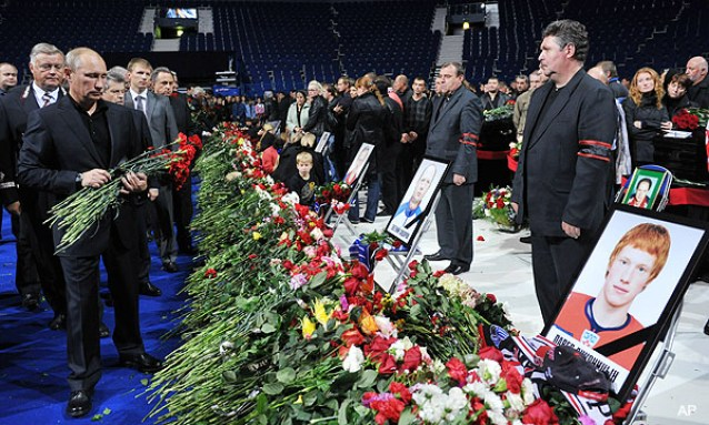 Russian Prime Minister Vladimir Putin, left, lays flowers during a memorial ceremony for the victims of the Russian plane crash in the Arena in Yaroslavl, 150 miles (240 kilometers) northeast of Moscow in Russia, Saturday, Sept. 10, 2011. The chartered Yak-42 jet crashed Wednesday into the banks of the Volga River moments after takeoff from an airport near Yaroslavl. The crash killed 43 people, including 36 players, coaches and staff of the Lokomotiv Yaroslavl ice hockey team, many of whom were European national team and former NHL players. It was one of the worst aviation disasters ever in sports, shocking Russia and the world of hockey. The team had been heading to Minsk, Belarus to play its opening game of the Kontinental Hockey League season. (AP Photo/RIA Novosti, Alexei Nikolsky, Pool)