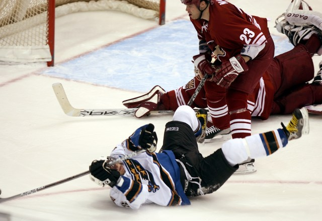 Washington Capitals left winger Alex Ovechkin, front, of Russia, shoots the puck from over his head after being checked to the ice by Phoenix Coyotes defenseman Paul Mara, center, past Coyotes goalie Brian Boucher, rear, for a goal in the third period of NHL action Monday, Jan. 16, 2006, in Glendale, Ariz. The Capitals defeated the Coyotes 6-1.(AP Photo/Paul Connors)