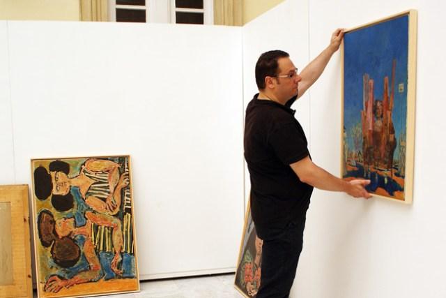 Martín Robles coloca los cuadros de la nueva muestra de Federico Castellón.