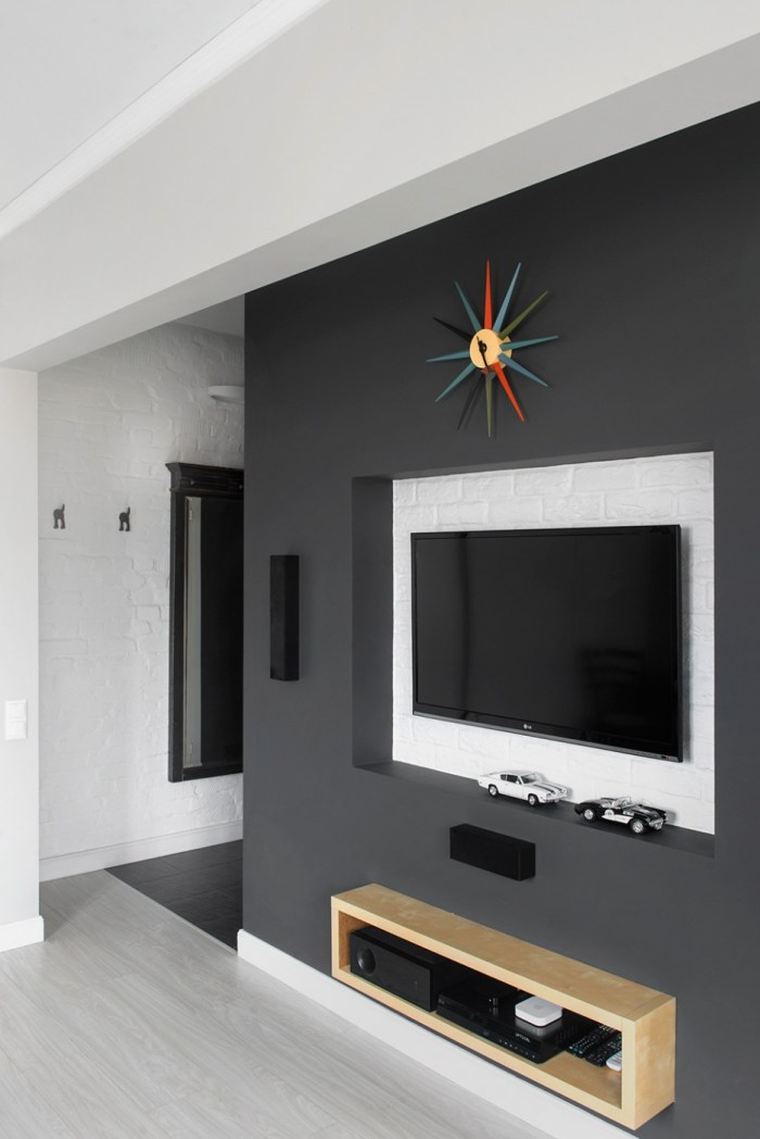 Dark-Grey-Interior-Wall-with-Built-in-Wall-TV-Frame-and-Floating-Wooden-Shelving-at-Family-Room-Decor-with-the-Small-Car-Toys-and-Open-Clock-936x1402